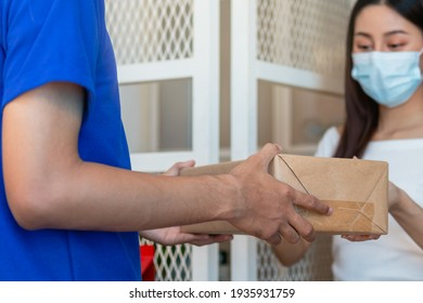 Young asian woman, client received a delivery of cardboard box, parcel from delivery, postman, wearing face mask due to lockdown, quarantine of COVID 19 at the door, entrance of her home, house.