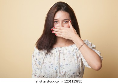 Young Asian woman close her mouth with hand on beige background
