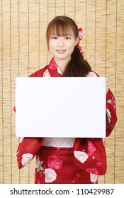 Young asian woman in clothes of kimono holding a blank white board