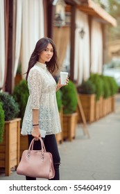 Young Asian woman with coffee cup and phone standing against street blurred cafe background. Fashion business photo of beautiful girl in white dress looking at camera
