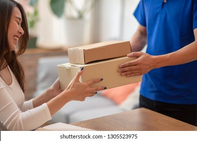 Young Asian woman customer feeling happy when receiving package from delivery service company staff.