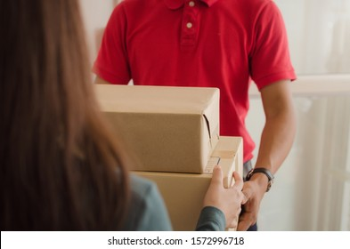 young asian woman customer receive parcel post box from home delivery service man in red uniform at home, express home delivery service, cargo shipping, transport logistics and online shopping concept