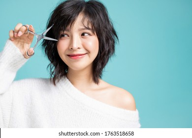 Young Asian woman cutting her bangs by herself isolated image on studio background