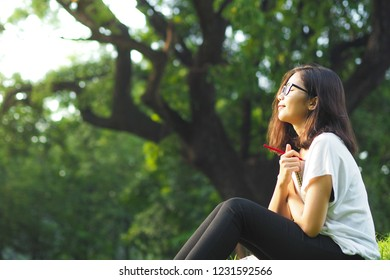 Young Asian woman with a diary in hands at outdoor