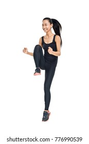 Young Asian woman doing fitness exercises and happy smiling. Energetic athletic girl practicing aerobics or dancing gymnastics. Full-length portrait of cheerful sportswoman isolated on white