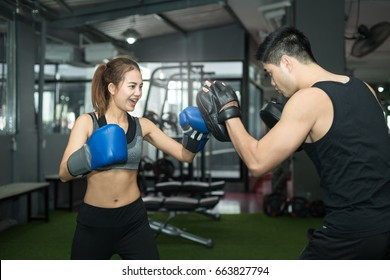 Young asian  woman doing kickboxing training with her coach.