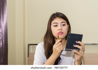 Young Asian woman is doing makeup by herself.