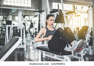 Young asian woman doing situp or crunches in gym,Female exercise muscular her stomach