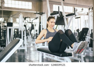 Young asian woman doing situp or crunches in gym,Female exercise muscular her stomach,Happy and smiling