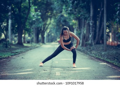 Young Asian woman doing some warm up exercises and streching before running at the park in morning with sunlight