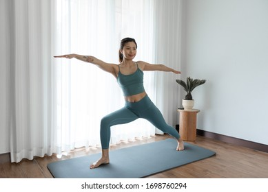 A young Asian woman doing yoga at home