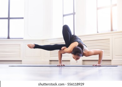 Young asian woman doing yoga pose and asana ashtavakrasana. Fitness girl enjoying yoga indoors in sport clothes, working out in gym class