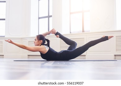 Young asian woman doing yoga pose Dhanurasana, bow pose, asana. Fitness girl enjoying yoga indoors in sport clothes, working out in gym class