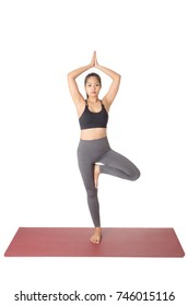 young asian woman doing yoga in Vrikshasana or Tree yoga pose on the mat isolated on white background, exercise fitness, sport training and healthy lifestyle concept