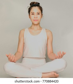 Young asian woman doing yoga exercises,pose sitting on a floor isolated on grey background, exercise fitness, sport training and healthy lifestyle concept,Low contrast and soft focus.