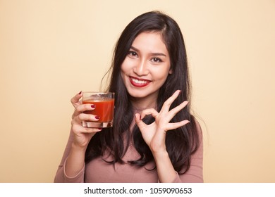 Young Asian woman drink tomato juice on beige background