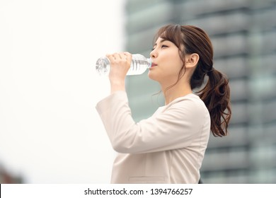Young asian woman drinking a bottle of water. Hydration concept. - Shutterstock ID 1394766257