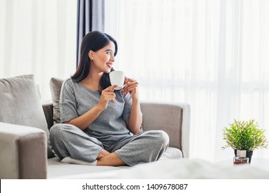 Young asian woman drinking coffee on a sofa bed at home