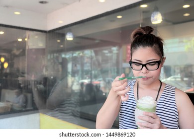 A young Asian woman drinking green Tea frappe.