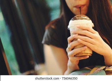 Young asian woman drinking ice coffee in cafe shop.