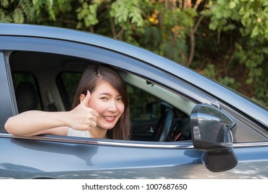 Young Asian woman driving car for her first drive with confidence