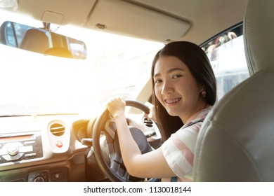 Young Asian woman driving car keeps wheel turning around smiling looking at passengers in back seat against sunset rays Light shine. Beautiful Smiling driver girl sitting in automobile back view.
