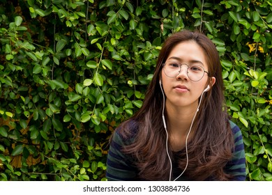 Young asian woman with earphone on green plant background.