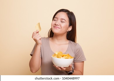 Young Asian woman eat potato chips on beige background