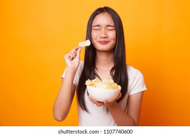 Young Asian woman eat potato chips on bright yellow background