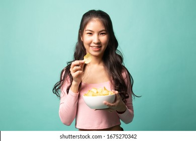 Young Asian woman eat potato chips on cyan background