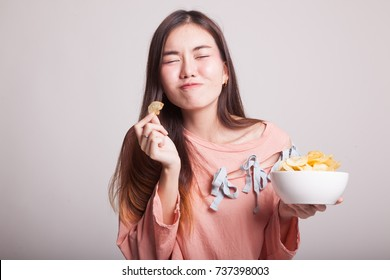 Young Asian woman eat potato chips on gray background