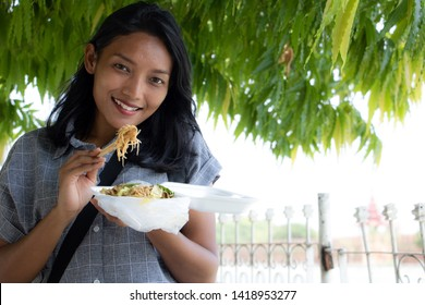 A young Asian woman eat typical Burmese food on a street in Mandalay, Myanmar. Tourist eat noodle from fast food restaurant.