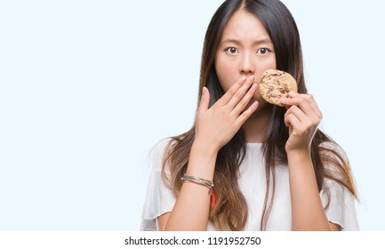 Young asian woman eating chocolate chip cookie over isolated background cover mouth with hand shocked with shame for mistake, expression of fear, scared in silence, secret concept