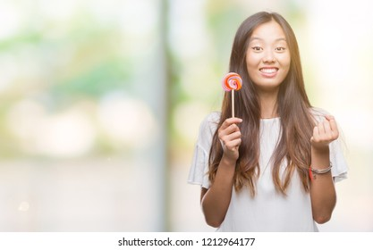 Young Asian Woman Eating Lollipop Candy Over Isolated Background Screaming Proud And Celebrating Victory And Success