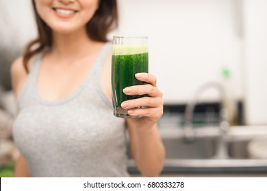 Young asian woman enjoy healthy vegetarian smoothie for weight loss and detox
