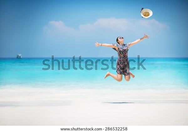Young Asian woman enjoy on a beach, Happy holidays vacation outdoors. Jumping.