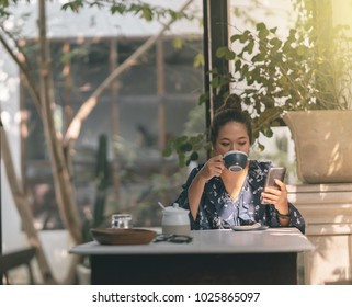 Young asian woman enjoying coffee in cozy cafe. Female holding cup of cappuccino. Blurred interio