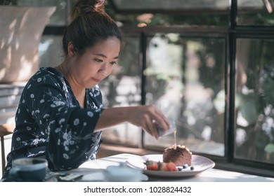 Young asian woman enjoying coffee and chocolate cake in cozy cafe.