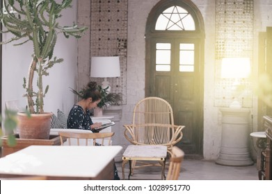 Young asian woman enjoying coffee in cozy cafe. Female holding cup of cappuccino. Blurred interior