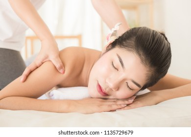 Young asian woman enjoying relaxing back massage in spa. Body care, skin care, wellness, alternative medicine and relaxation Concept.