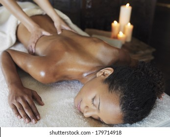 Young Asian woman enjoying a spa and beauty treatment and massage as she lies on her stomach with the masseuse manipulating her back muscles with a background of burning candles