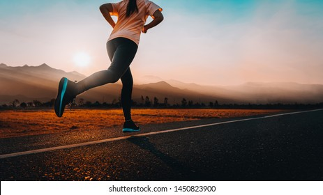Young asian woman enjoys running outside with beautiful summer evening in the countryside.