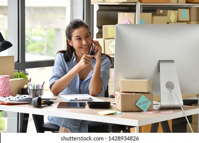 Young Asian woman entrepreneur/ Business owner using a smartphone and working with computer at home