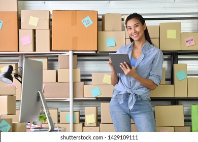 Young Asian woman entrepreneur/ Business owner working at home for online shopping and preparing package product
