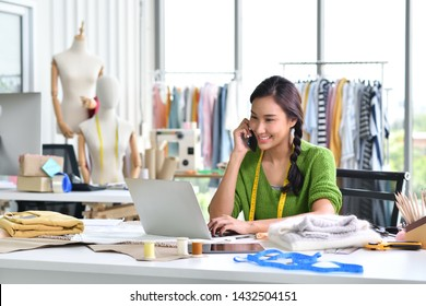 Young Asian woman entrepreneur / fashion designer working in studio