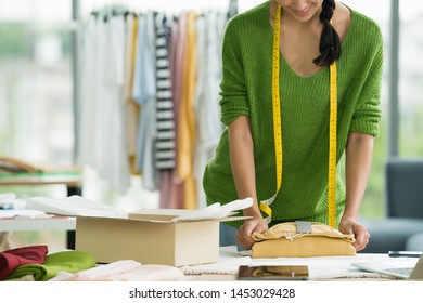Young Asian woman entrepreneur / fashion designer working in studio and packing and sending product