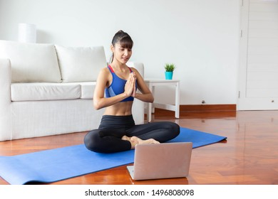 Young asian woman exercising yoga at home in a living room with computer notebook