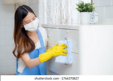 Junge asiatische Frau in Gesichtsmaske und Handschuhe Reinigung Haus im Zimmer, Hausmeister wird mit Stoff, Hausmädchen und Service, Arbeiter polieren Staub im Haus, Hausarbeit und häusliche, Lifestyle-Konzept wischen.