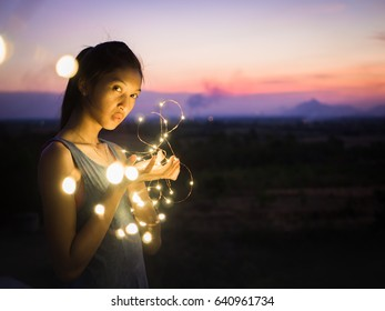 Young asian woman with fairy lights in sweet sunset.