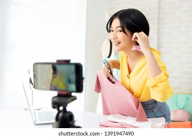 Young Asian woman fashion vlogger trying on earring live streaming online with smartphone